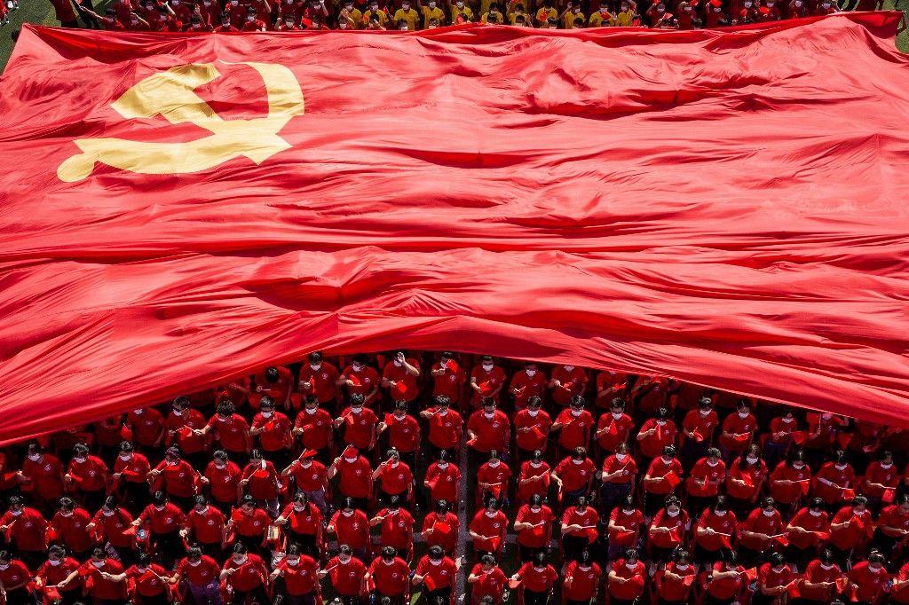 Des étudiants universitaires arborent un drapeau du Parti communiste chinois pour marquer le 100e anniversaire du parti à Wuhan, le 10 septembre 2021.