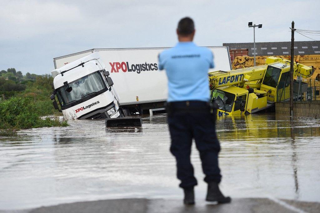 Un officier de gendarmerie français regarde deux camions bloqués sur une route inondée à Codognan, dans le département du Gard, en région Occitanie, dans le sud de la France, le 14 septembre 2021 à la suite de fortes pluies
