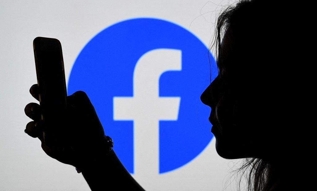 Une personne regarde un smartphone avec un logo de Facebook affiché en arrière-plan, le 17 août 2021, à Arlington, en Virginie.