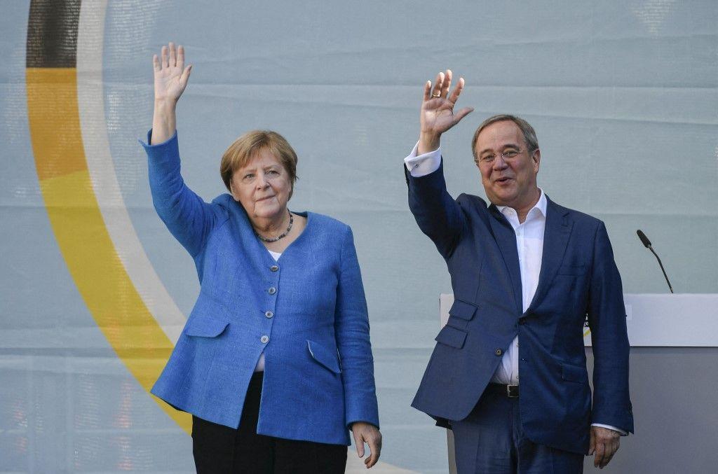 Le leader de la CDU, Armin Laschet, et la chancelière allemande Angela Merkel saluent leurs partisans lors d'un rassemblement à Aix-la-Chapelle, le 25 septembre 2021.