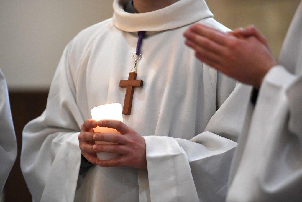Un enfant de chœur tient une bougie lors d'une messe à Brest, le 27 mars 2021. Une commission indépendante a rendu son verdict dans un « rapport général » sur les abus sexuels au sein de l'Eglise.