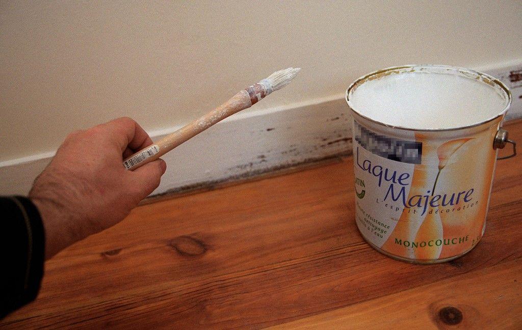 Une personne s'apprête à effectuer des travaux de peinture à son domicile à l'aide d'un pinceau.