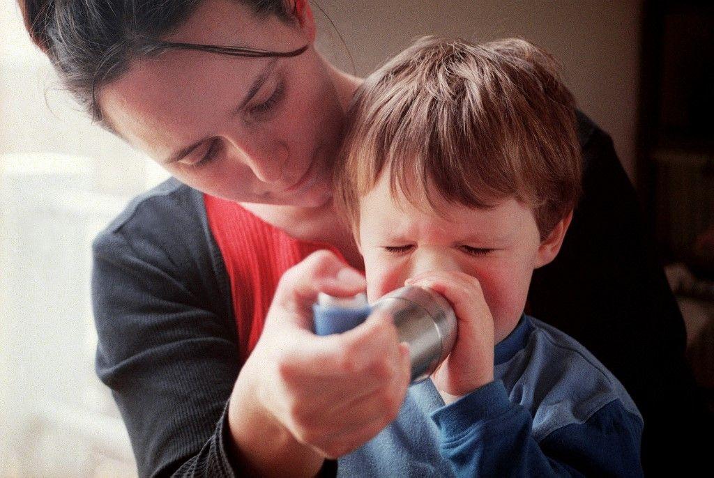 Une jeune maman fait inhaler de la ventoline à son enfant souffrant d'asthme pour prévenir une éventuelle crise, le 26 février 2002.