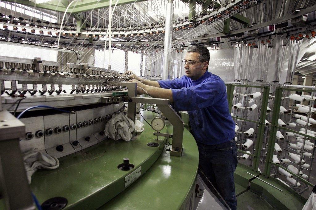 Un technicien de la société Chamtex (production de tissus) amorce les bobines d'une tricoteuse, le 26 avril 2005 à Bobigny.