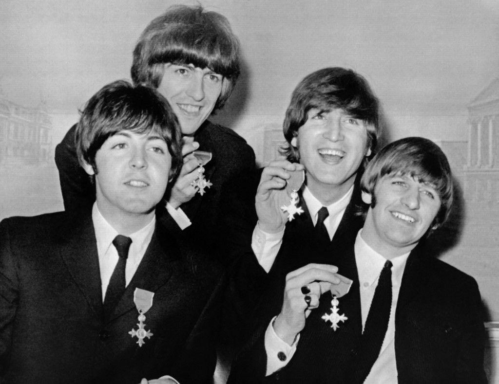 Les membres du groupe The Beatles, Paul McCartney, George Harrison, John Lennon et Ringo Starr, brandissent leurs prix MBE lors d'une conférence de presse le 26 octobre 1965 au palais de Buckingham à Londres.