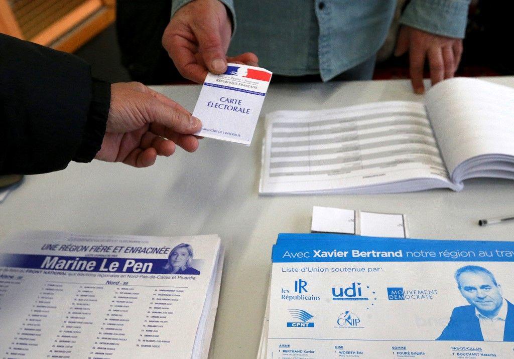 Un électeur présente une carte d'électeur lors du second tour des élections régionales dans la région Nord-Pas-de-Calais le 13 décembre 2015 dans un bureau de vote de Saint-Quentin.