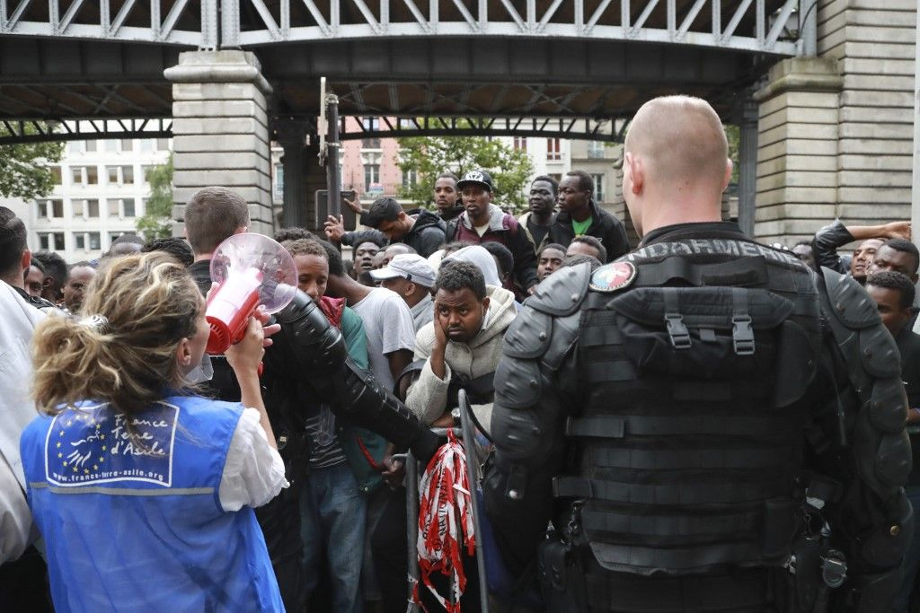 Des migrants à Paris écoutent une femme, membre d'une association.