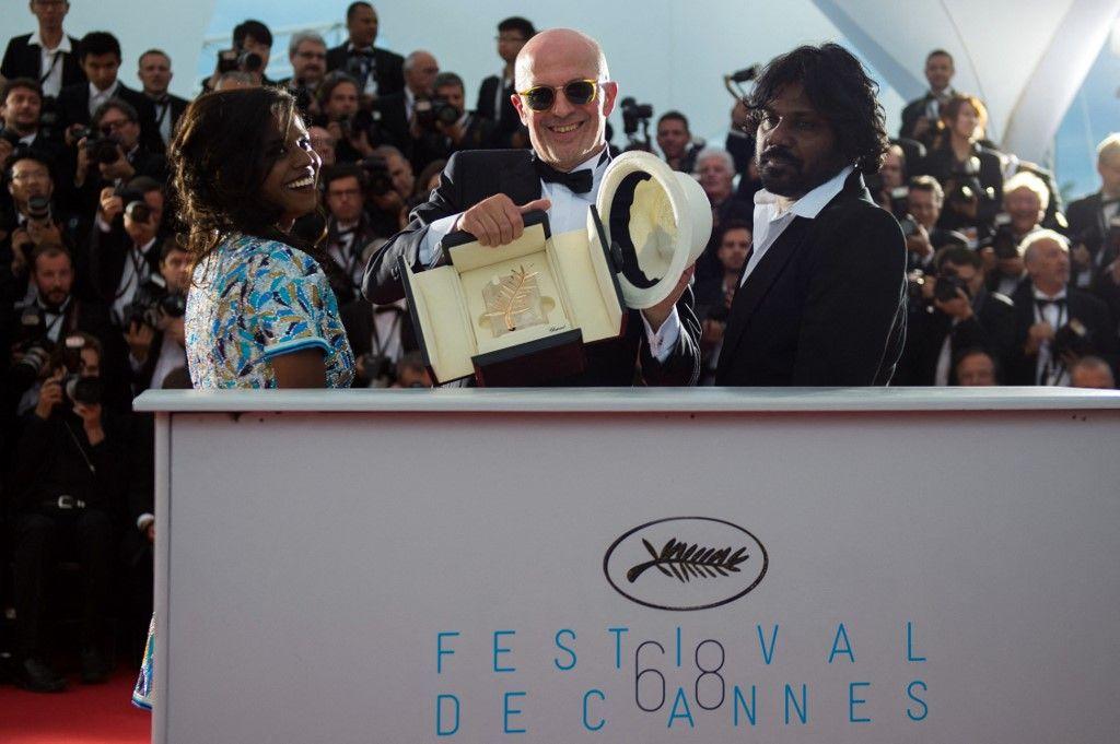 """Le réalisateur Jacques Audiard pose avec l'actrice Kalieaswari Srinivasan et l'acteur Jesuthasan Antonythasan après avoir reçu la Palme d'Or pour son film """"Dheepan"""" lors du 68e Festival de Cannes, le 24 mai 2015."""