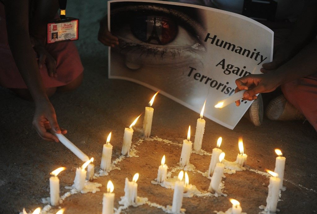 Des écoliers indiens allument des bougies lors d'une veillée dans une école de Siliguri le 16 novembre 2015, à la suite des attentats terroristes en France, à Paris.