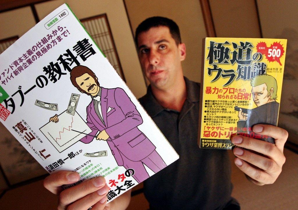 Une photo du journaliste Jake Adelstein qui présente un manga sur les yakuzas et un livre de gestion d'entreprise écrit par un ancien chef du crime. La récession a durement frappé les yakuzas.
