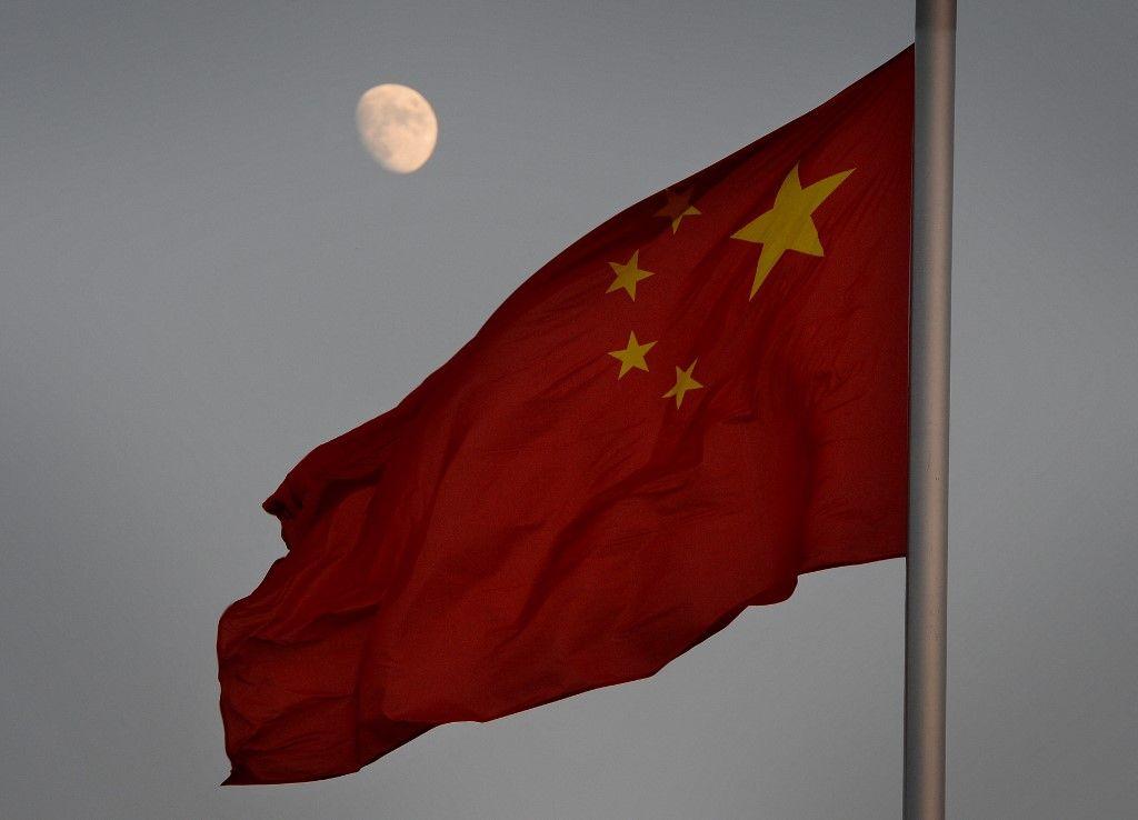 Le drapeau chinois devant une vue de la Lune sur la place Tiananmen à Pékin.