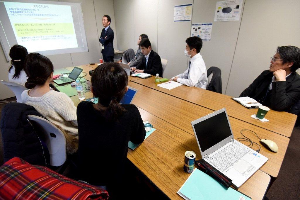 Les employés du groupe japonais de brasseries et de distilleries Suntory assistent à une réunion dans leurs bureaux à Tokyo le 24 février 2017.