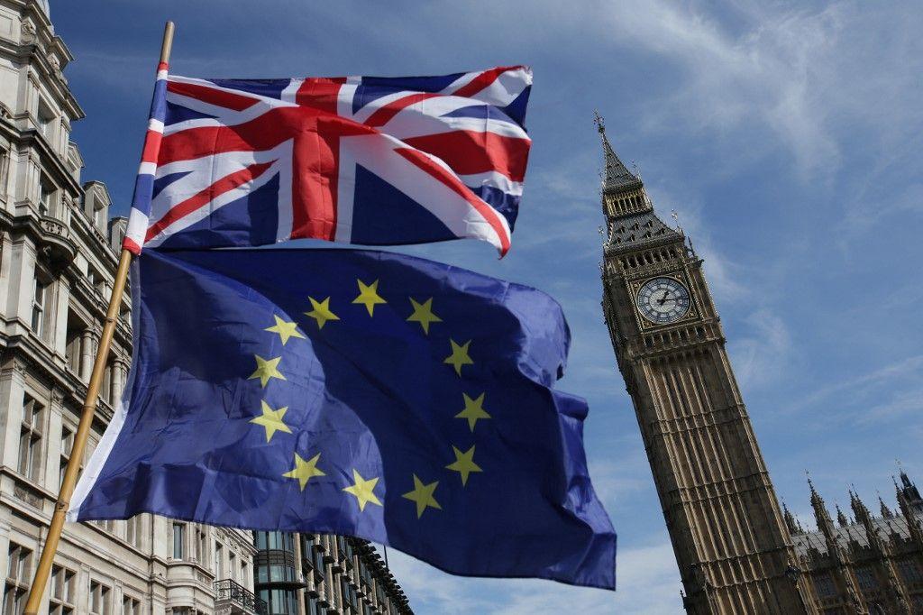 Un drapeau de l'UE et un drapeau du Royaume-Uni devant Big Ben et les Chambres du Parlement dans le centre de Londres en mars 25 décembre 2017.