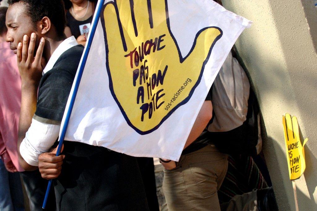 """Des gens brandissent des pancartes """"touche pas à mon pote"""" lors d'une manifestation organisée par """"SOS Racisme"""" contre les violences des militants du FN, le 15 avril 2007 à Lyon, après une agression."""