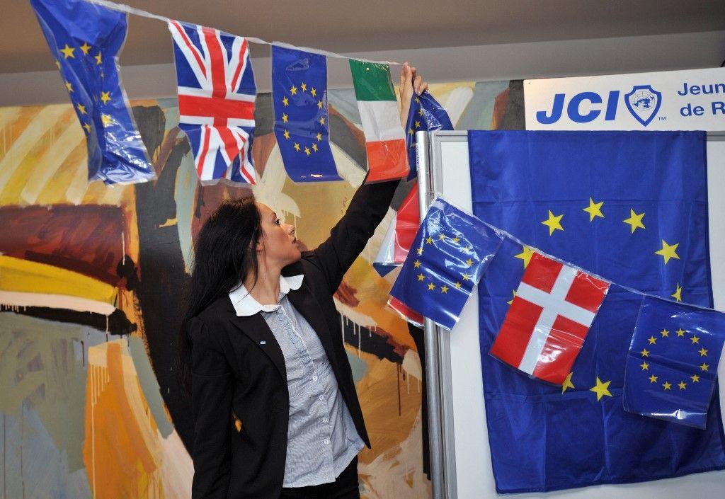 """Une jeune femme installe une guirlande ornée de drapeaux des pays membres de l'Union européenne, le 11 octobre 2008 à Nantes, avant le début de la séance de clôture de la manifestation """"Paroles d'Européens"""";"""