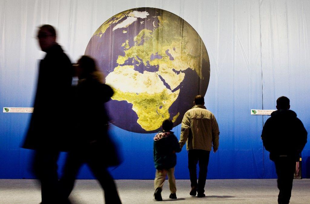 Des personnes dans un musée lors d'une exposition sur le réchauffement climatique et les enjeux environnementaux.