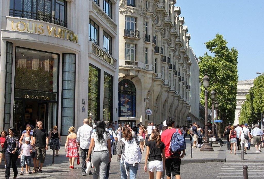 Des personnes passent devant le magasin Louis Vuitton, sur l'avenue des Champs Elysées, le 16 août 2009, à Paris.