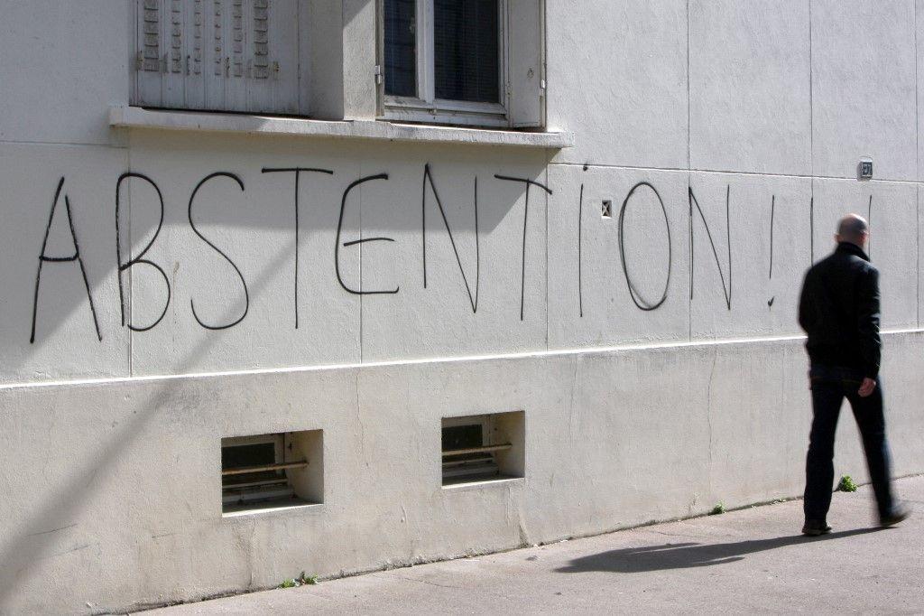 """Un homme marche le long d'un mur sur lequel le mot """"abstention"""" a été tagué, le mardi 16 mars 2010 à Caen."""