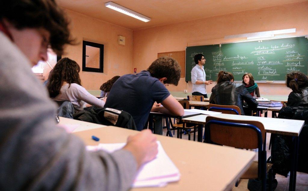 Des lycéens écoutent attentivement et prennent des notes lors d'un cours.