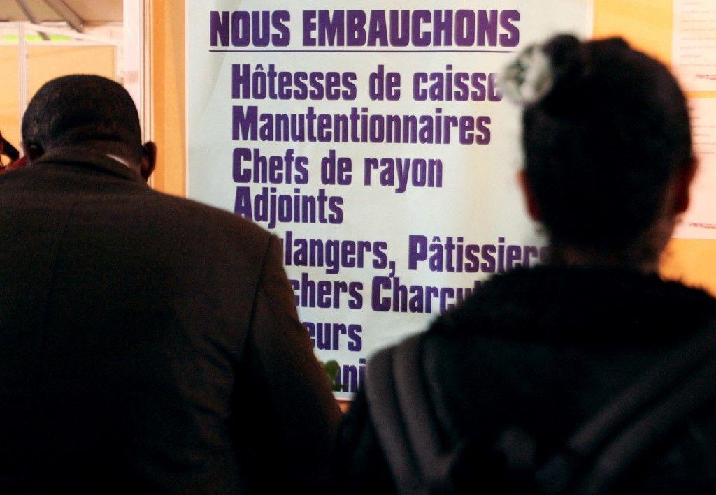 """Des personnes regardent des annonces au forum """"Paris pour l'emploi""""."""