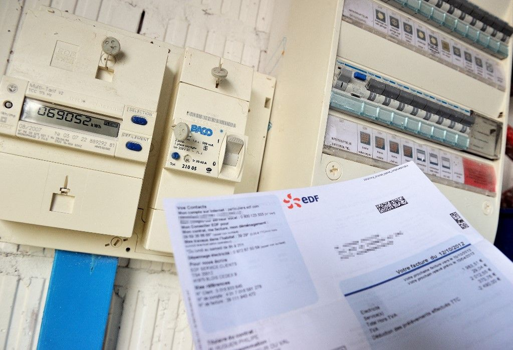 Une personne consulte son compteur électrique avec sa facture d'électricité d'EDF à la main, à Godewaersvelde, dans le nord de la France, en juillet 2013.