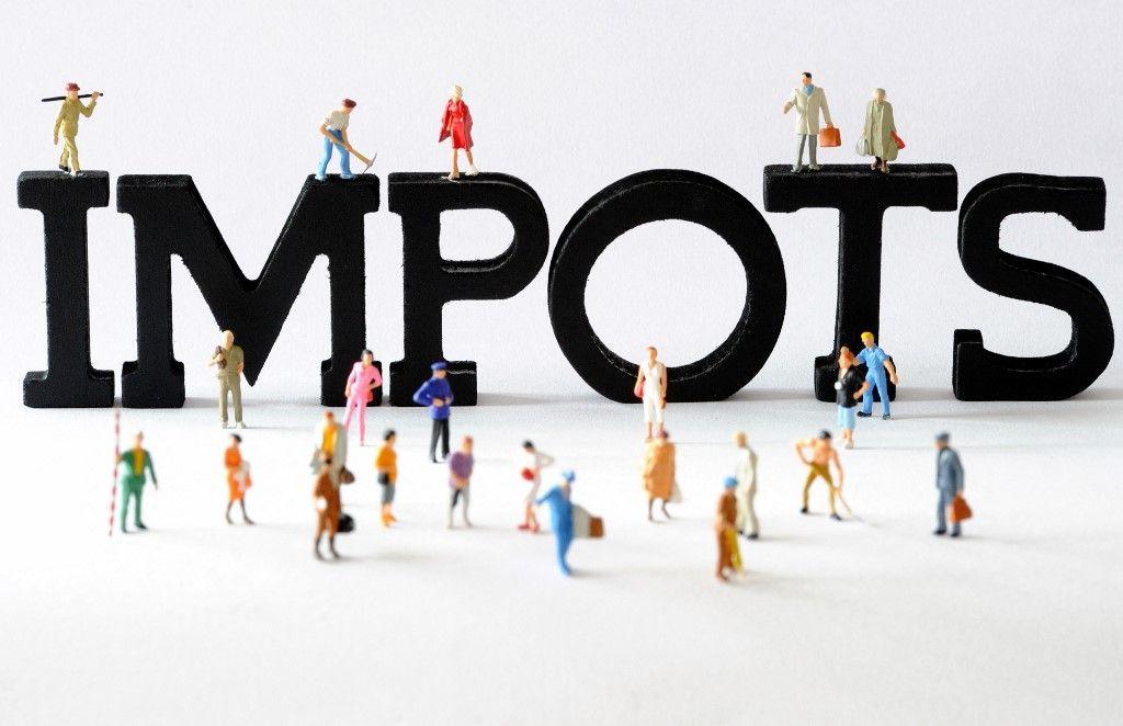 """Photo prise le 07 août 2013 à Lille de figurines posées devant des lettres composant le mot """"impôts""""."""