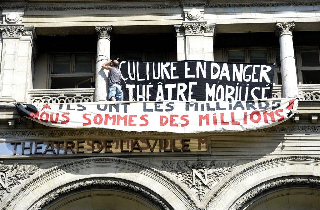 """Des artistes et des intermittents du spectacle installent des banderoles au sommet du théâtre """"Théâtre de la ville"""" à Paris le 29 juin 2014."""