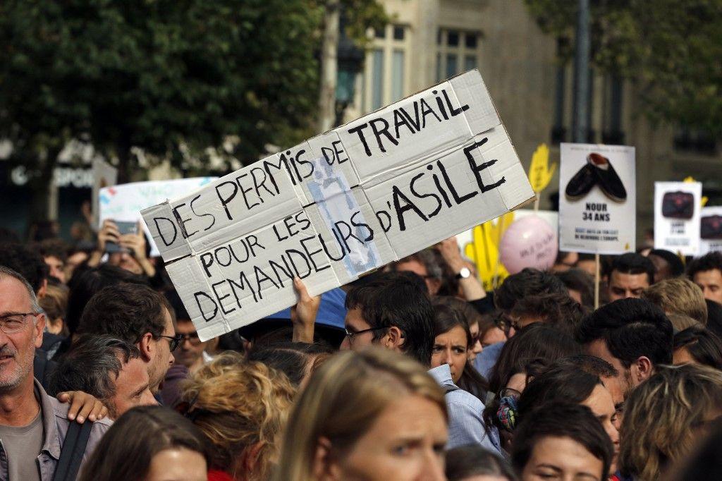 """Une personne tient une pancarte indiquant """"Des permis de travail pour les demandeurs d'asile"""" lors d'une manifestation de soutien aux migrants sur la Place de la République à Paris le 5 septembre 2015."""