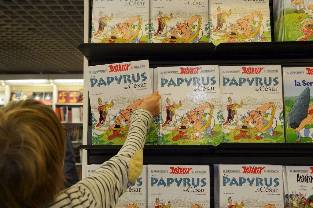 """Un enfant prend l'album d'Astérix, """"Astérix et le parchemin manquant"""" (Le Papyrus de César""""), le 22 octobre 2015 à Paris. 5000 ouvrages, dont des albums de Tintin et Astérix, ont été retirés au Canada"""