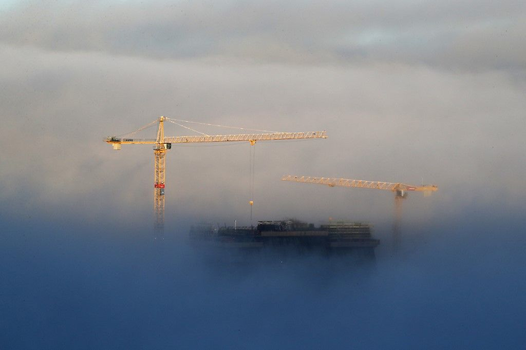 Des grues de construction et le toit du nouveau musée Munch en construction émergent au-dessus d'un épais brouillard recouvrant le centre d'Oslo le 15 novembre 2017.