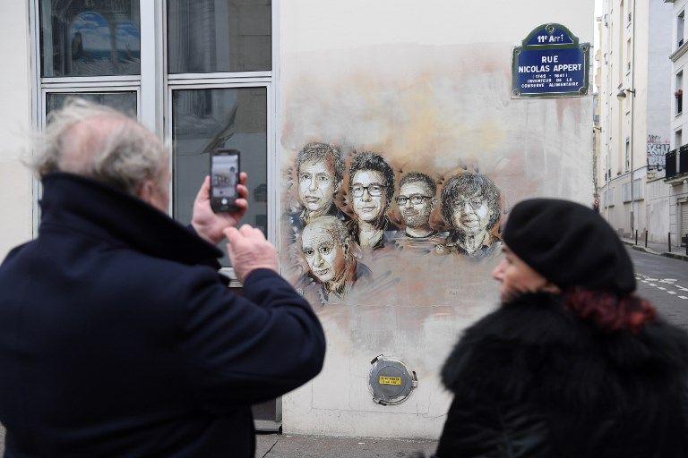 Des passants photographient la fresque en hommage aux membres de la rédaction de Charlie Hebdo tués lors de l'attentat de janvier 2015, devant les anciens locaux de la rédaction dans le XIe arrondissement de Paris.