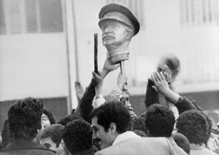 Photo datée du 16 janvier 1979 de manifestants défilant dans les rues de Téhéran avec la statue du père du Chah, Reza Chah, durant la révolution iranienne.