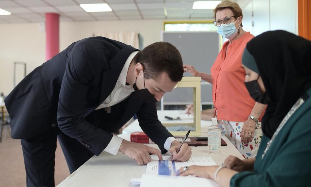 Le candidat à l'élection régionale d'Ile-de-France du Rassemblement National, Jordan Bardella, signe le registre après avoir déposé son bulletin de vote dans un bureau de vote de Saint-Denis, le 20 juin 2021.