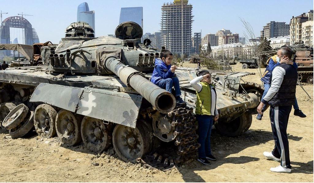 Un garçon salue devant un char alors qu'il visite le parc des trophées militaires qui présente du matériel militaire saisi aux troupes arméniennes lors de la guerre du Haut-Karabakh, à Bakou, le 15 avril 2021.