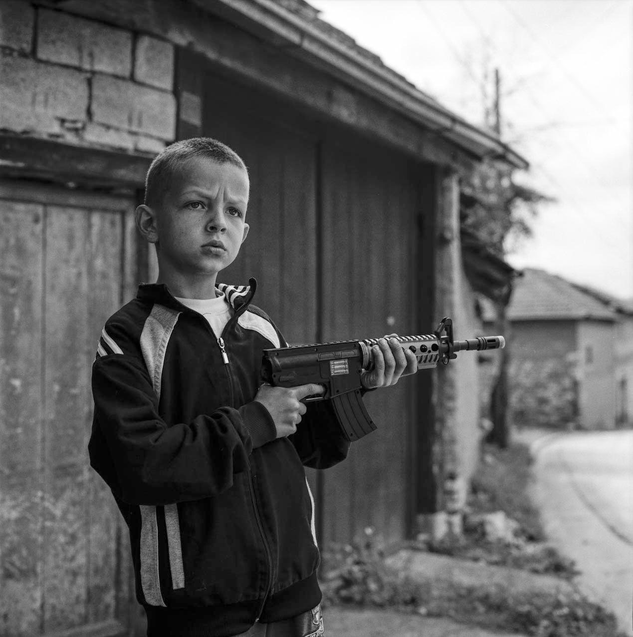 Petit garçon serbe au fusil factice dans les rues de son village au Kosovo (avril 2016).