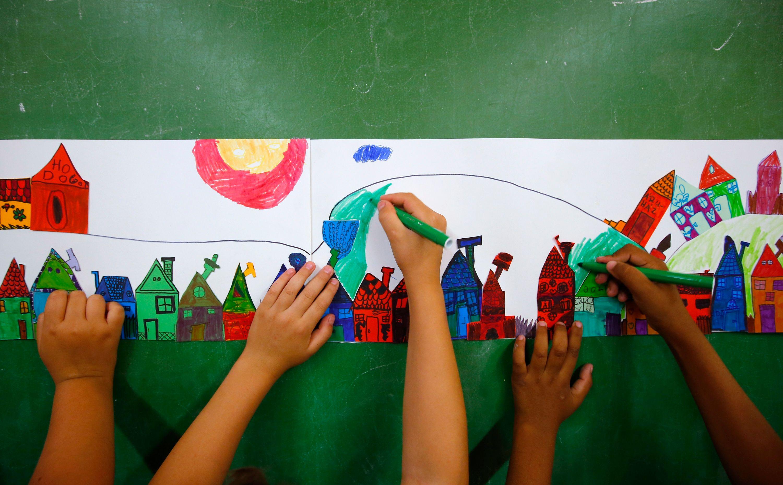 Enfants dessinant sur un mur lors d'un cours d'éveil.