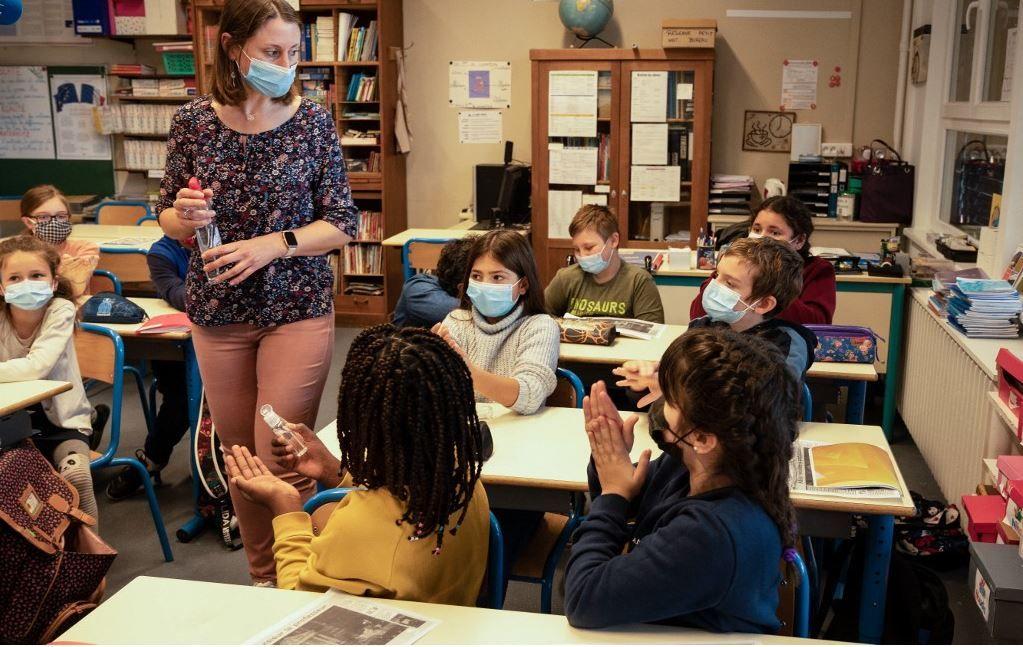 Une enseignante vaporise du gel hydroalcoolique sur les mains des élèves, en novembre 2020, alors que les élèves reviennent en classe.