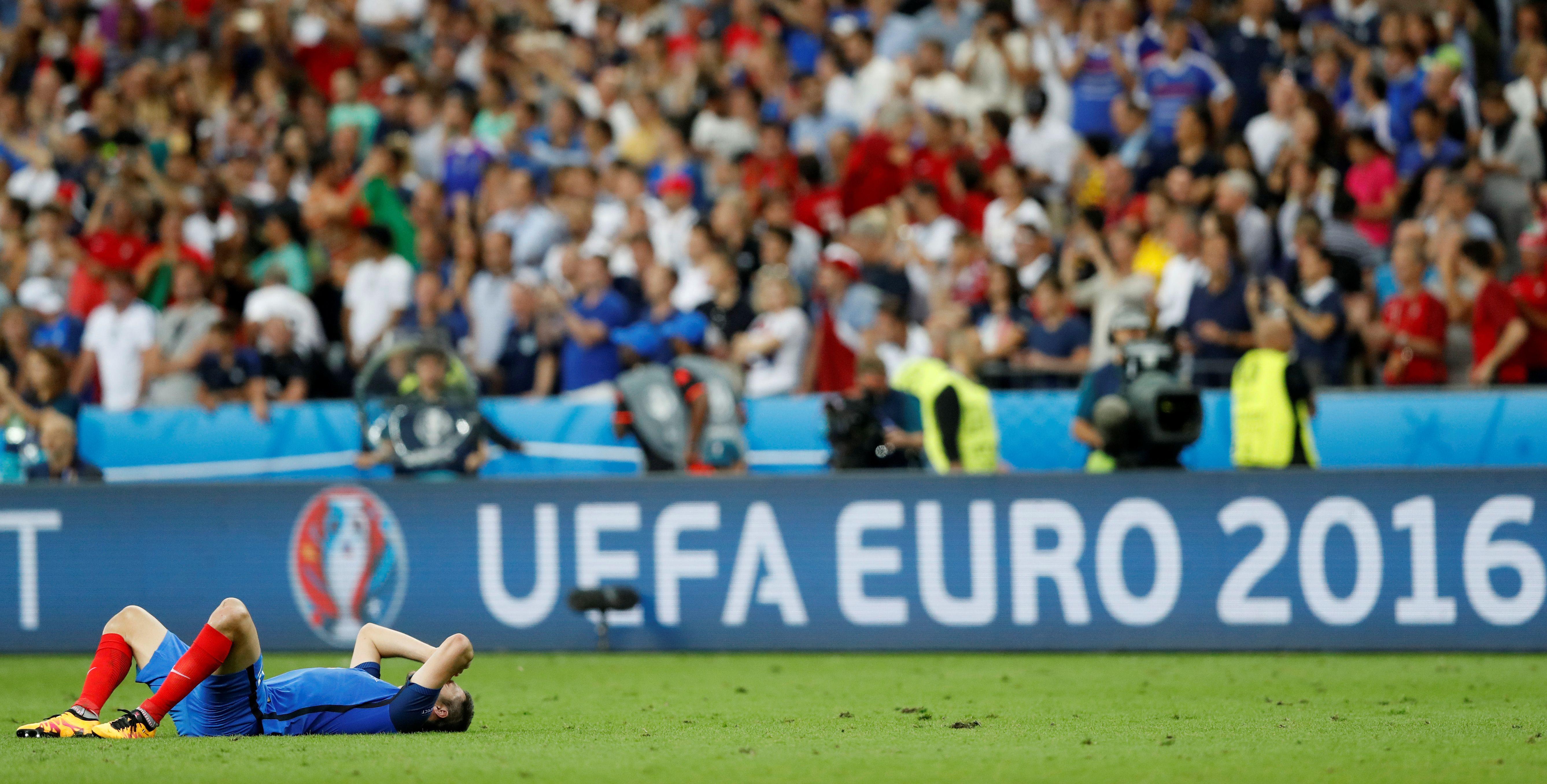 """La colère et la tristesse du n°10 Français, André-Pierre Gignac, allongé sur la pelouse du stade de France après la défaite des Bleus face au Portugal en finale de l'Euro 2016 le 10 juillet 2016, et qui parlera de """"cauchemar"""" à l'issue du match."""