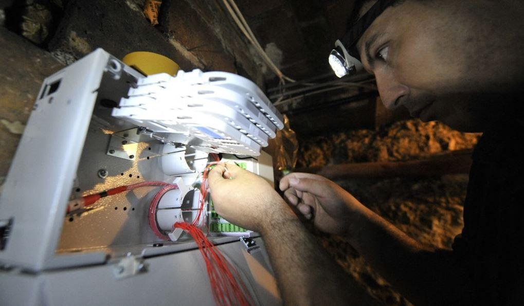 Un technicien connecte des câbles à fibres optiques dans une boîte de jonction d'un immeuble, le 22 juillet 2010 à Paris.