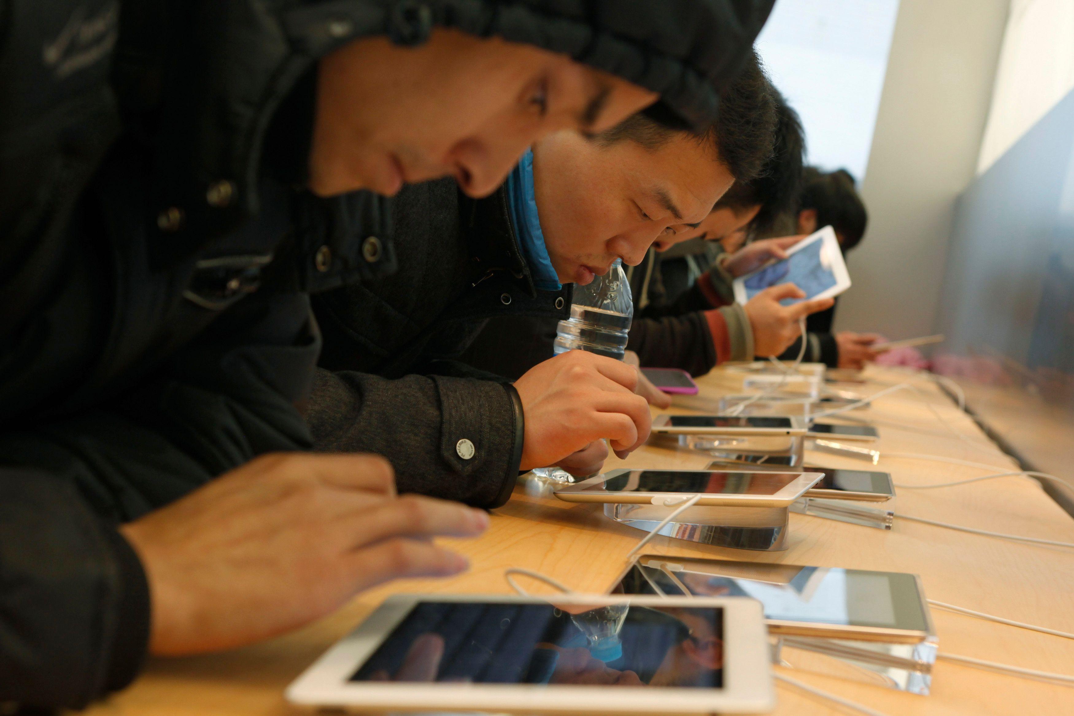 Des Chinois testant l'iPad dans un Apple store de Shanghai.