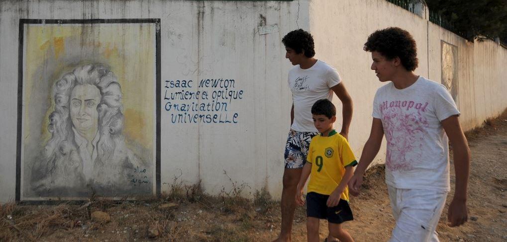 Des jeunes marchent devant un mur recouvert par des graffitis et des peintures à Tunis, dont une reproduction d'un portrait d'Isaac Newton, en juillet 2010.