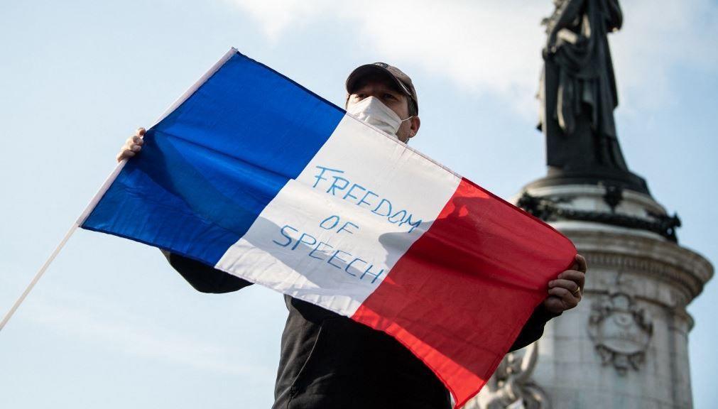 Un homme tient un drapeau français lors d'un rassemblement sur la place de la République à Paris le 18 octobre 2020, en hommage à Samuel Paty.