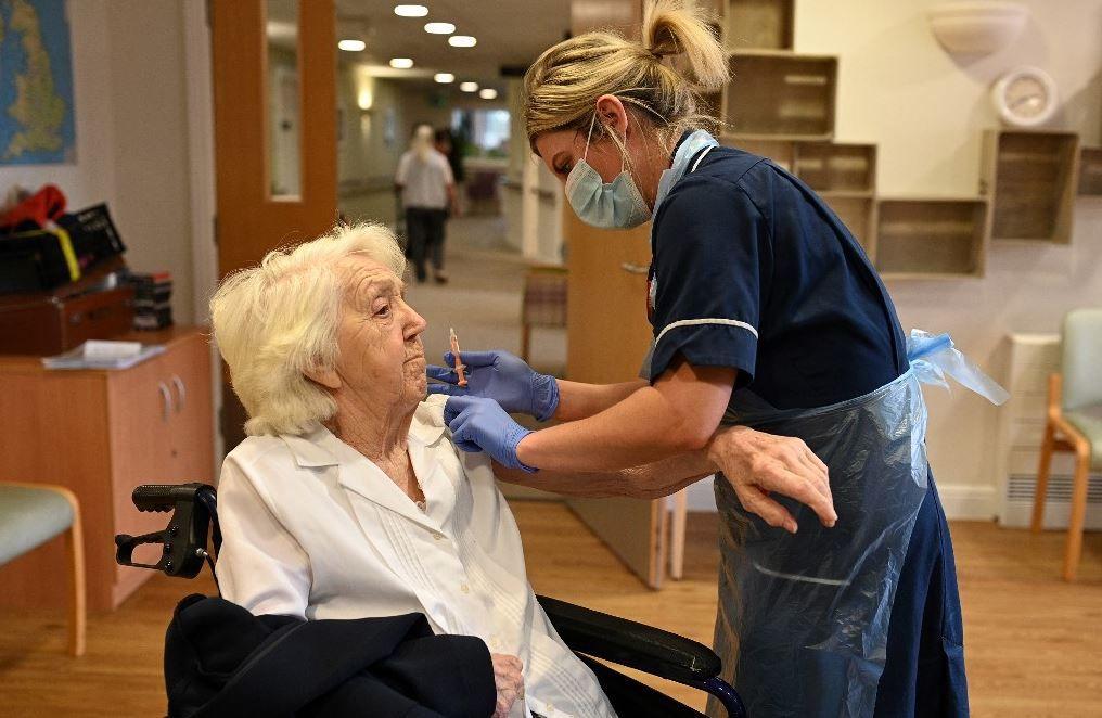 Une infirmière vaccine une résidente avec une dose du vaccin Oxford-AstraZeneca au foyer de soins Belong Wigan à Wigan, dans le nord-ouest de l'Angleterre, le 21 janvier 2021.