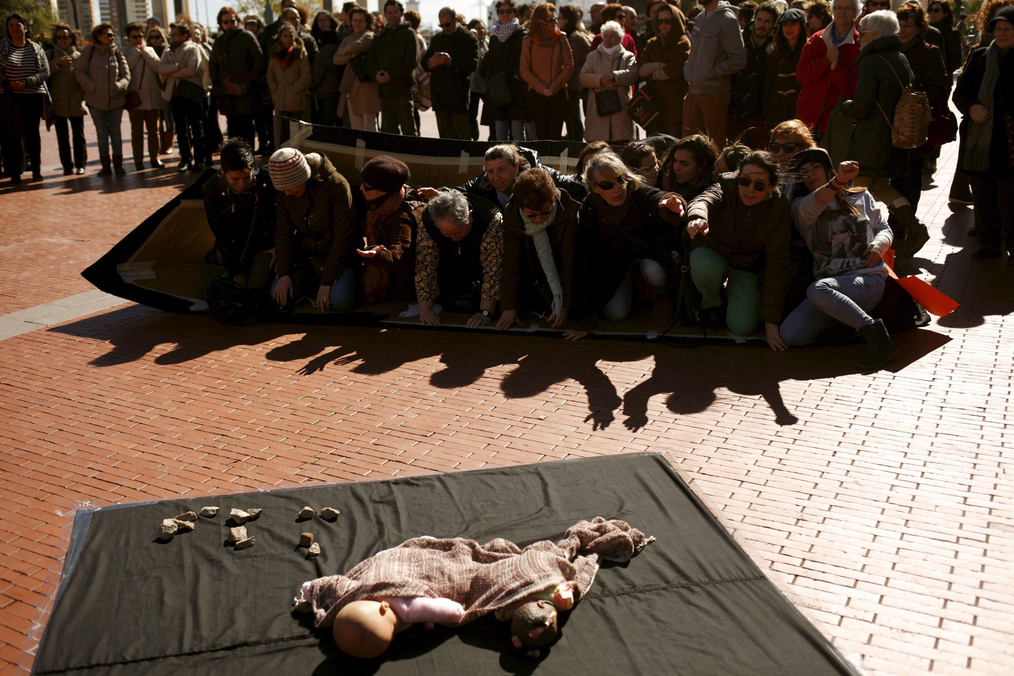 Reconstitution, à l'occasion d'une marche pour la paix à Malaga en Espagne le 27 février 2016, d'un naufrage de bateau de migrants, près d'une poupée représentant la mort tragique du petit syrien Aylan Kurdi, échoué sur les côtes de Turquie.