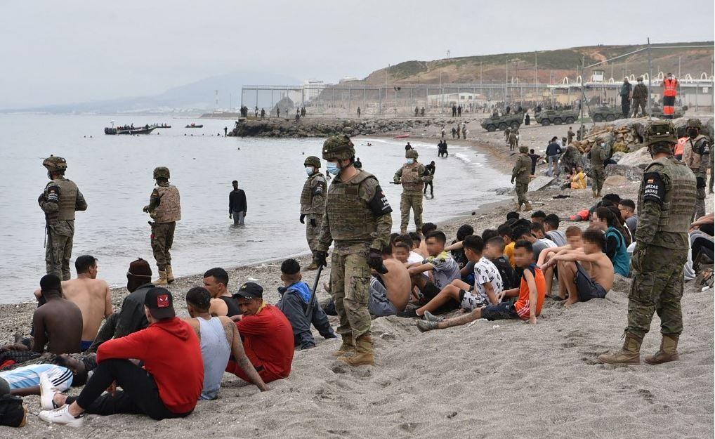 Des migrants, y compris des mineurs, arrivés à la nage dans l'enclave espagnole de Ceuta, se reposent alors que des soldats espagnols montent la garde le 18 mai 2021 à Ceuta.