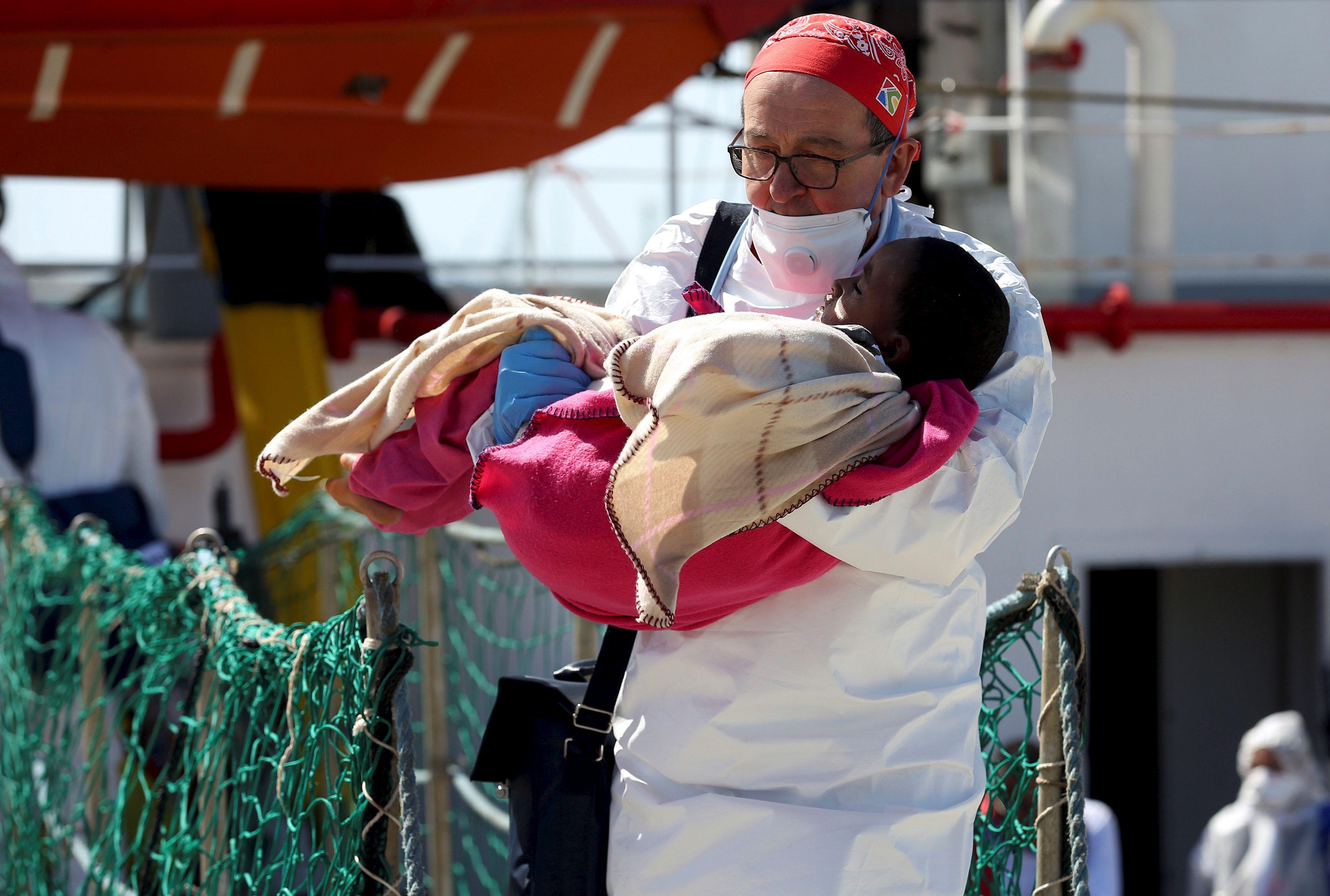 Un médecin porte un enfant alors que des migrants débarquent navires de Médecins Sans Frontières (MSF) dans le port de Pozzallo en Italie , le 25 Avril 2016.