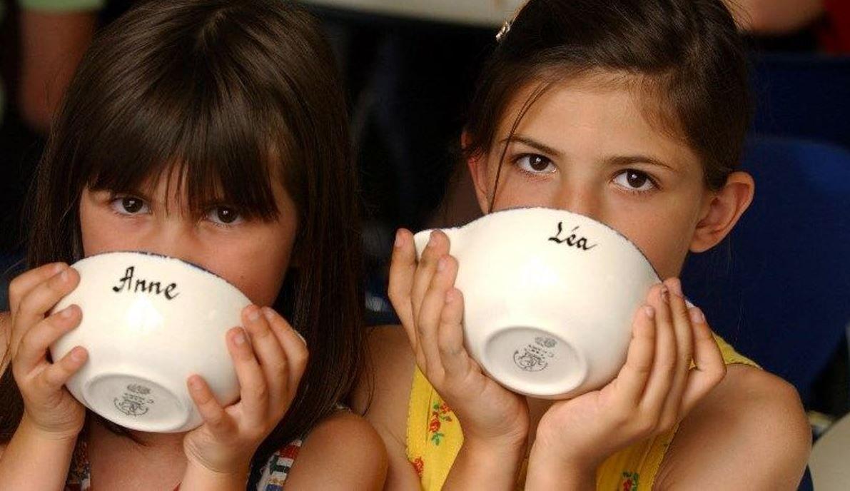 Deux jeunes filles boivent dans un bol avec leur prénom.