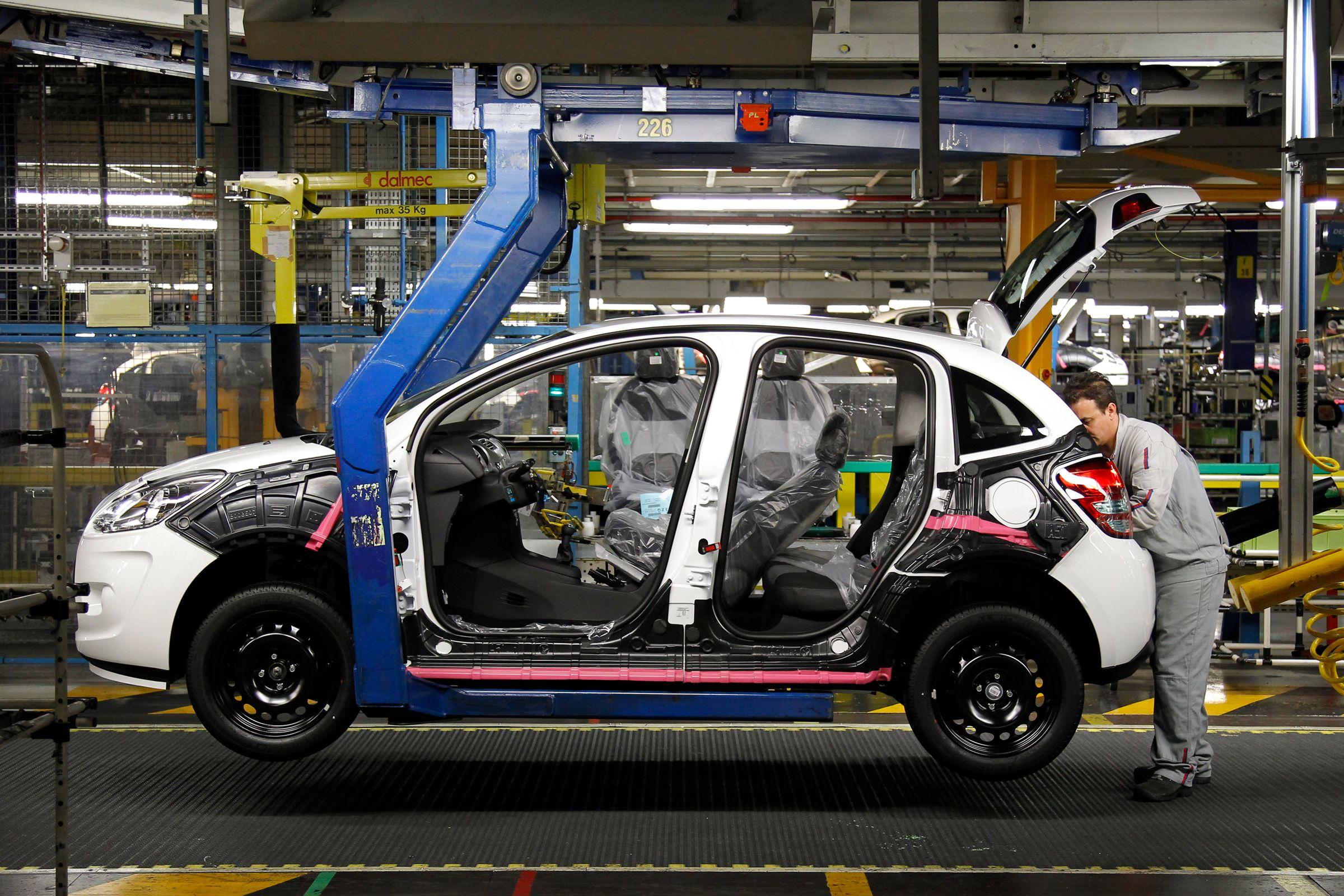 Un ouvrier travaillant dans une usine Peugeot.