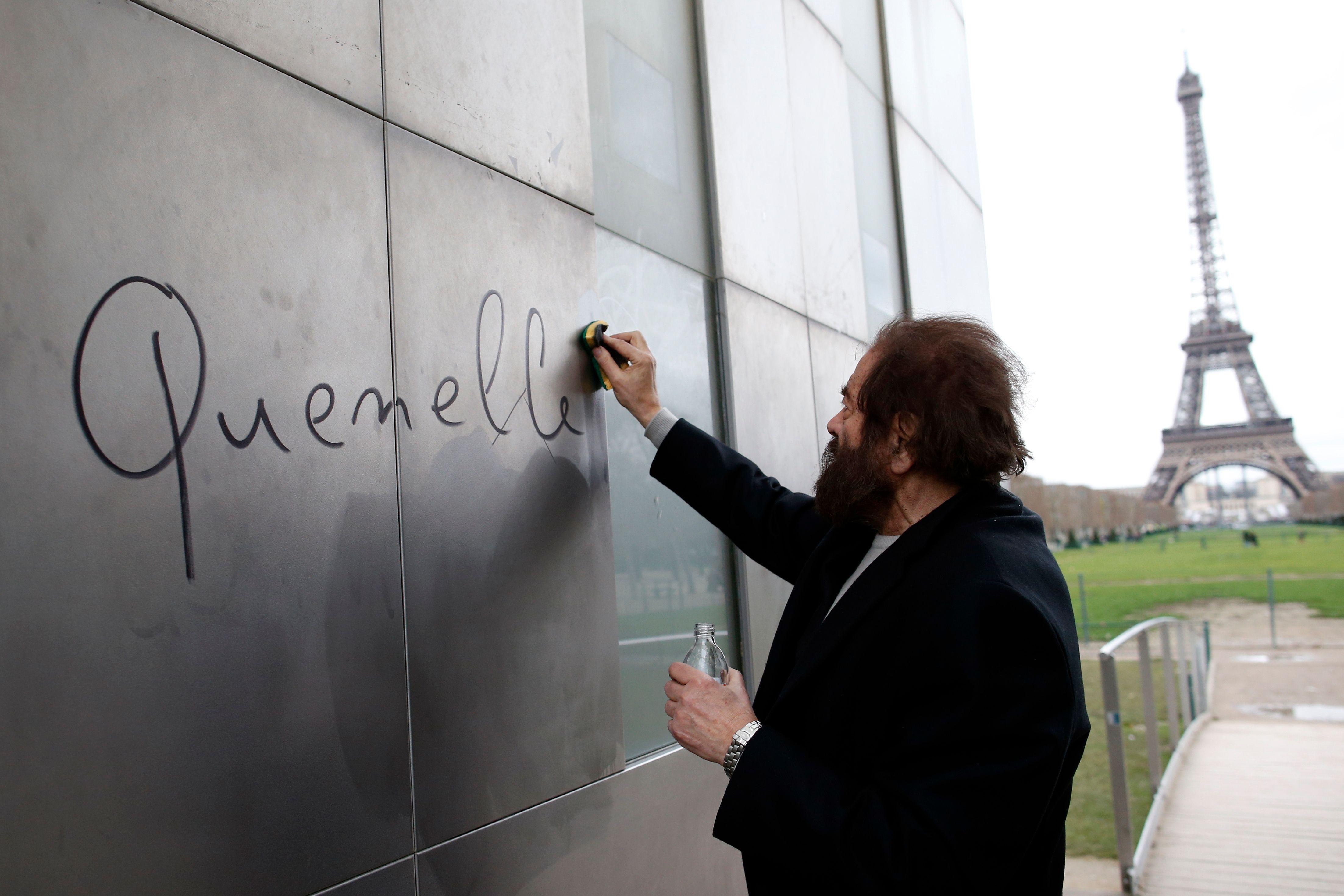 """L'auteur français Marek Halter nettoie le mot """"quenelle"""" écrit """"Le mur pour la paix"""" au Champs de Mars près de la Tour Eiffel à Paris."""