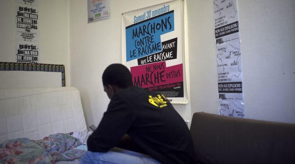 """Un étudiant sénégalais sans-abri et sans papiers à côté d'une affiche intitulée """"Marchons contre le racisme avant que le racisme ne nous envahisse"""" dans les locaux de la FIDL (Fédération Indépendante et Démocratique Lyceenne) à Paris en octobre 2014."""